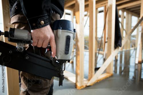 Obraz Midsection Of Professional Carpenter Holding Drill Machine - fototapety do salonu