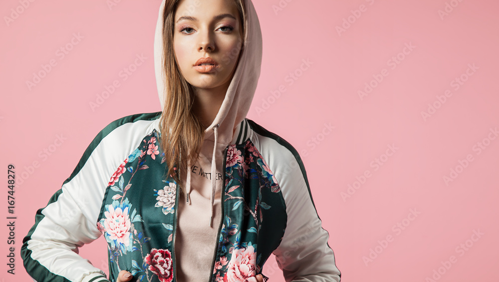 Fototapeta Fashionable beautiful young woman in a bomb jacket with floral print stands on a pink background