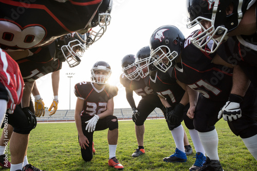 Tuinposter Tunnel Sportsmen standing in circle and planning strategy of game on football field.