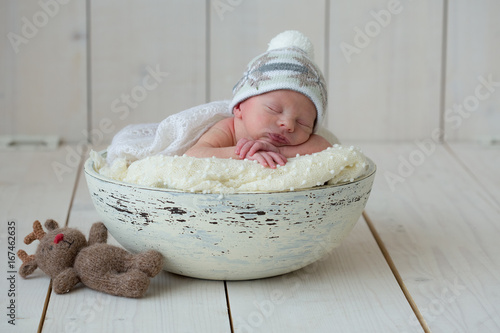 The newborn boy lies in a round bowl on a white plaid and sleeps sweetly with his hands under his head