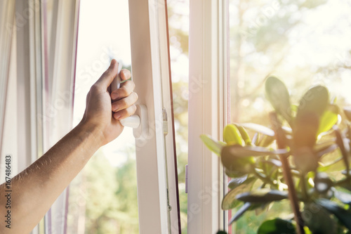 Fotografie, Obraz  hand open white plastic pvc window at home