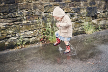 Child Playing In The Puddles On A Rainy Day