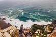 Traveler girl legs above cliff precipice and Atlantic ocean. Freedom, beautiful sea landscape