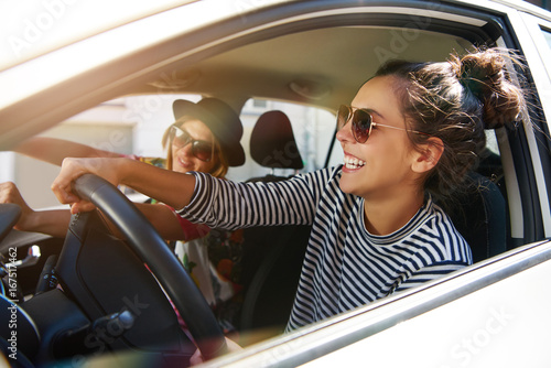 Poster Magasin de musique Two laughing young girlfriends driving together in a car