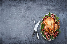Overhead Shot Of Golden Roasted Thanksgiving Turkey With Knife For Carving On A Platter Garnished With Parsley And Fresh Grapes Against A Rustic Background. Photo Shot In Flat Lay Style.