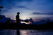 Silhouette of fisherman standing on boat,hold paddle,on sunset background.