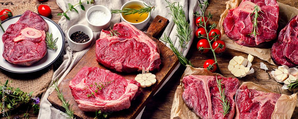 Fototapeta Raw beef meat on a dark wooden board.