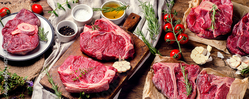 Raw beef meat on a dark wooden board. Canvas Print
