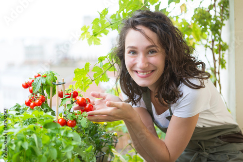 Fototapeta Young woman taking care of her plants and vegetables on her city balcony garden