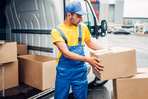 Cargo delivery service, male courier unload truck - Buy this stock
