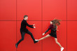 canvas print picture - Fight in jump. A man and a woman on a red background.