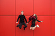 canvas print picture - jump. A man and a woman on a red background.