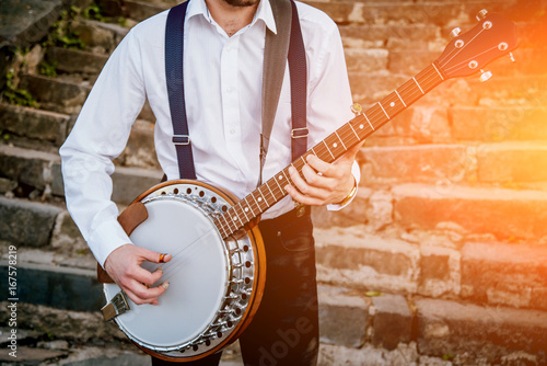 Fotografija View of musician playing banjo at the street