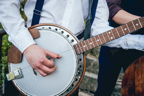 Fototapeta View of musician playing banjo at the street
