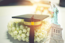 Concept Of Congratulate Graduate Study Success, Graduation Black Cap On Jasmine Garland,Education Certificate Of Abroad International, Diploma Or Certificate With Liberty Background, Work And Traver.