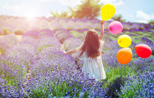 Pretty child girl runs with colorful balloons in lavender field summer freedom concept
