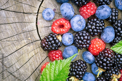 Freshly picked blueberries, blackberries and raspberries on a stump at the garden. Juicy and fresh berries with leaves on rustic wooden surface. Concept for healthy eating and nutrition.