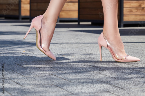 Beautiful slender legs tanned skin is shod in high-heeled shoes depilation body care catologue stylish fashion collection walks on the street health body care cream Tableau sur Toile