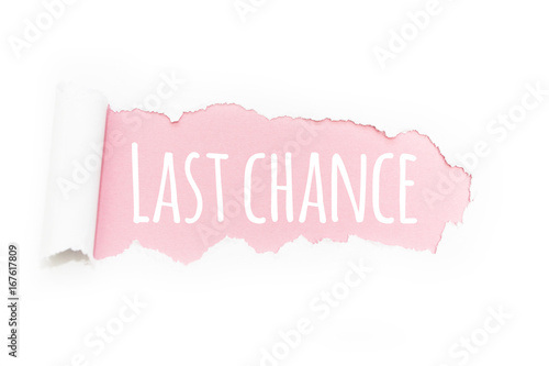 """Fotografía  A caption """"last chance"""" in the rupture of paper on a pink background"""