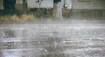 heavy rain drops falling on city street