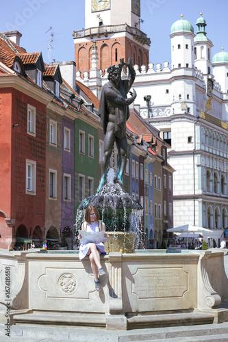 Plakat dziewczyna patrzy na mapę siedzącą przy fontannie przy Rynku Głównym w Poznaniu