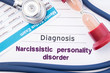 Diagnosis Narcissistic Personality Disorder (NPD). On psychiatrist or psychologist table is paper with inscription Narcissistic personality disorder near psychiatric report, hourglass and stethoscope