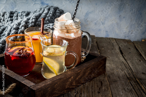 Photo sur Toile The Selection of various autumn traditional drinks: hot chocolate with marshmallow, tea with lemon and ginger, white pumpkin spicy sangria, mulled wine. On wooden rustic table, copy space, selective focus