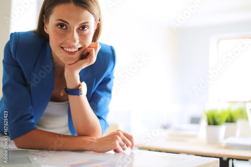 Fototapety, obrazy: Woman sitting on the desk with laptop.
