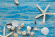 Sea star and shells on wooden blue background. Place for text. Top view.