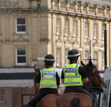 Two Female Police Officers On Horseback Patrol In A City.