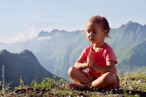 Fotografiet  Little cute girl meditating on top of mountain
