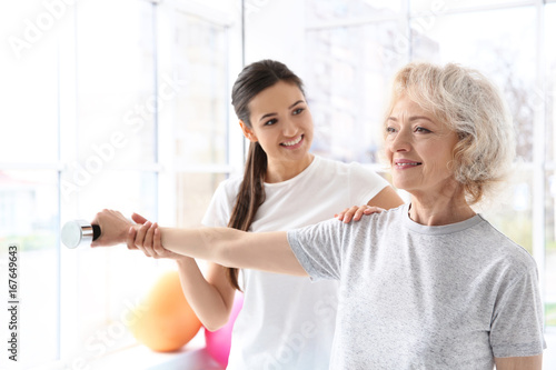 Fotografía  Physiotherapist working with elderly patient in modern clinic