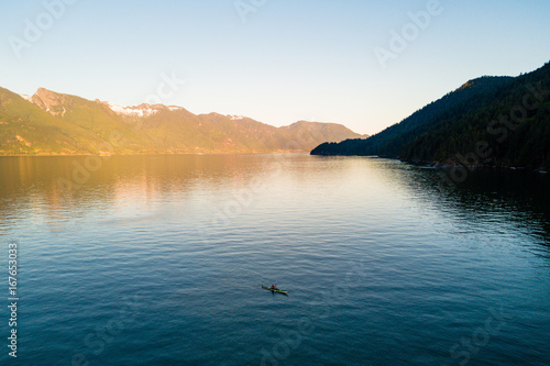Papiers peints Beige Aerial shot of kayaker on lake with mountains while sunset