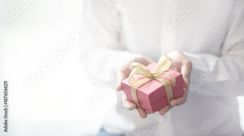 Fotografering  Closeup, Woman hand holding red gift box with copy space background, female giving gift, New year holidays and greeting season concept