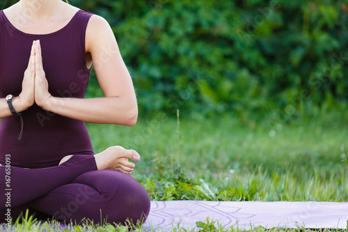 Young fitness woman practicing yoga lotus pose on the field with green grass, healthy lifestyle concept, copy space.
