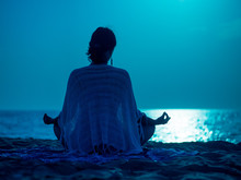 Yoga Under Full Moon Over Night Ocean Or Sea Beach. Young Woman's Meditation