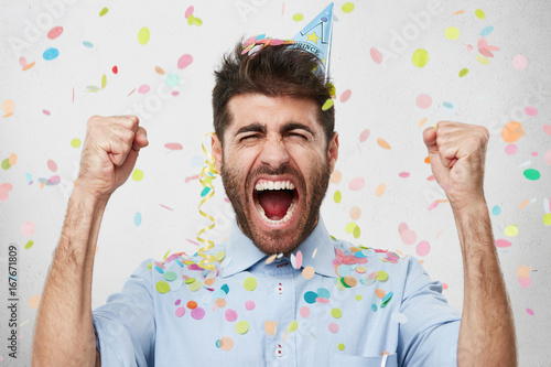 Joyful bearded man in formal clothes and holiday cap, clenching his fists with happiness, celebrating his birthday, having good mood. Satisfied male posing against white background with color pieces