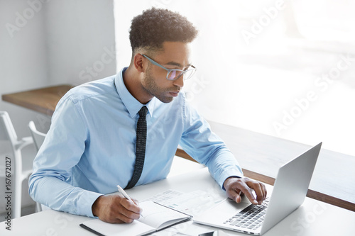 Garden Poster Handsome young dark-skinned manager with stubble wearing eyeglasses and blue shirt with tie having concentrated look while working on presentation using laptop computer, writing down in notebook