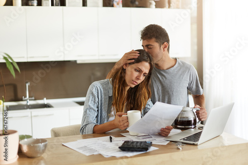 Frustrated woman studying sheet of paper in kitchen, drinking coffee and trying Wallpaper Mural