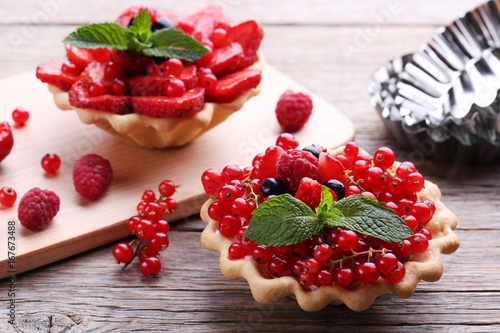 Dessert tartlets with berries on grey wooden table Poster