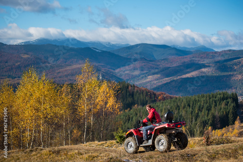 Landscape of mountains, forest and blue sky with man on red quad bike at autumn sunny day. The concept of an active holiday in the mountains