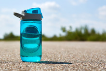 A Sports Bottle With Water Stands On The Road. Concept Of Sport And Refreshment