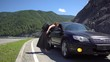 A tourist girl hitchhiking a car on a mountain road and sits down in it 4k.