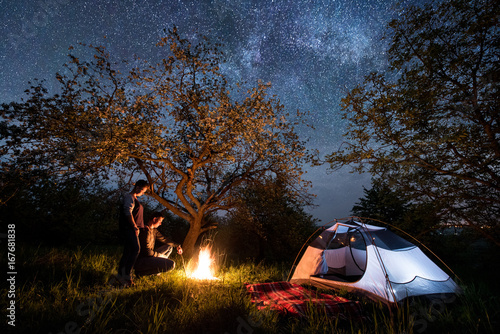 Fototapeta Romantic couple tourists standing at a campfire near tent under trees and beautiful night sky full of stars and milky way. Night camping obraz na płótnie
