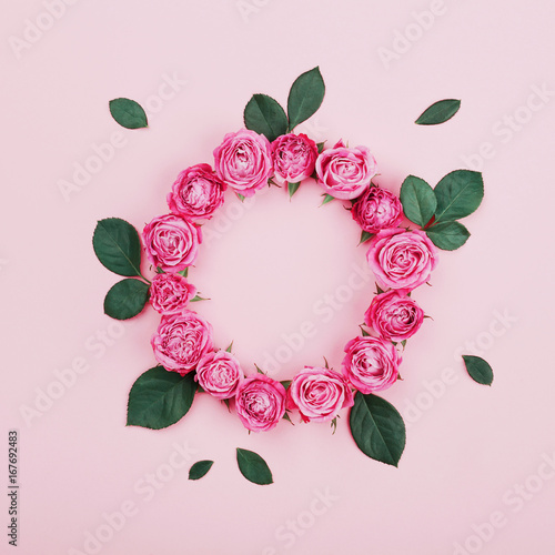 Foto op Canvas Bloemen Floral frame made of pink rose flowers and green leaves on pastel background top view. Flat lay styling. Fashion and creative composition.