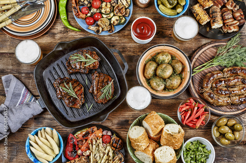 In de dag Grill / Barbecue Outdoors Food Concept. Appetizing barbecued steak, sausages and grilled vegetables on a wooden picnic table with copy space, top view