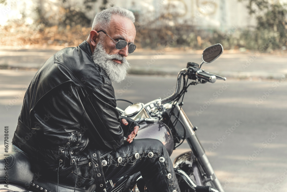 Fototapeta Interested old man ready for riding motorcycle