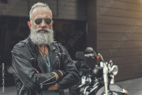 Confident old man having rest near bike