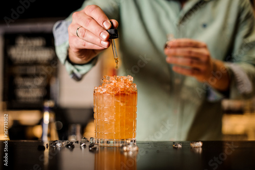 Photo Bartender adds bitter to cocktail