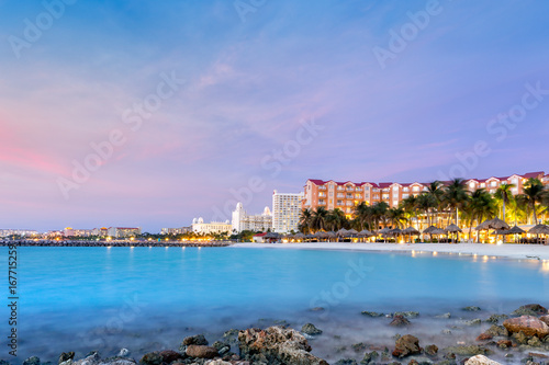 Foto op Plexiglas Caraïben High Rise hotel area in Aruba at dusk. Palm trees in motion suggest the windy weather, a well known characteristic of this island, located on the southern fringes of the Caribbean